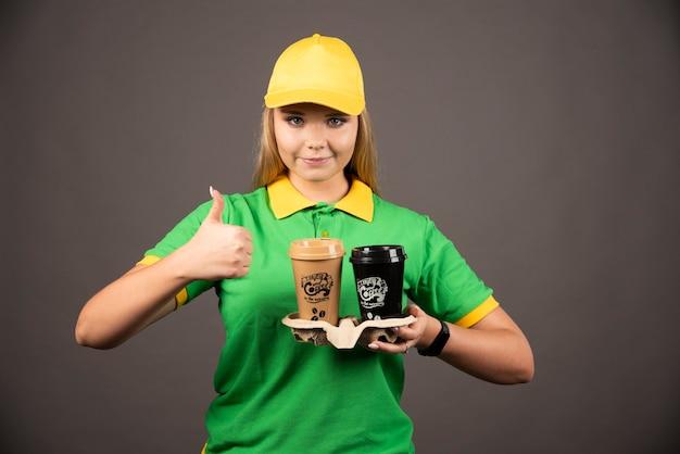 Доставщик, держа чашки кофе и показывая большой палец вверх.