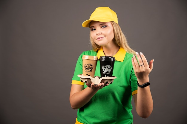 Доставщик, держа чашки кофе на черной стене.