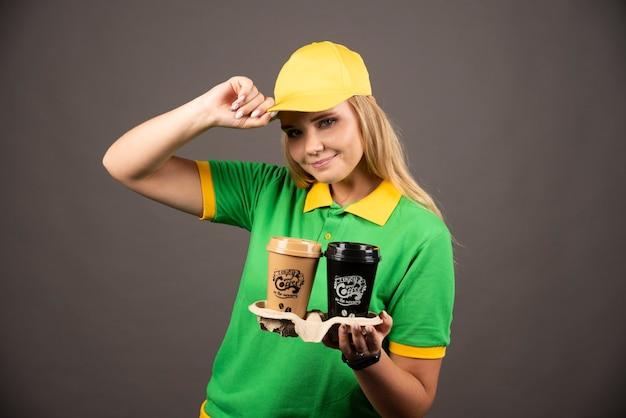 黒い壁にコーヒーのカップを保持している配達員。