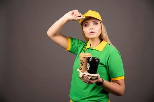 暗い背景にコーヒーのカップを保持している配達員。高品質の写真