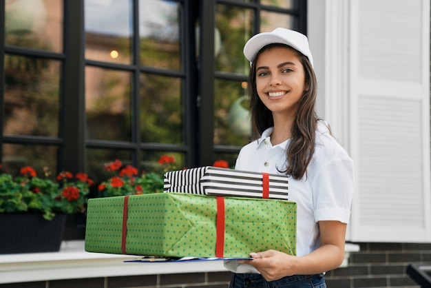 Deliverywoman holding gift boxes and folder