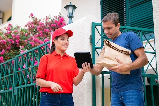Deliverywoman holding tablet and showing client order data. concentrated caucasian man receiving paper bag and reading information on gadget.