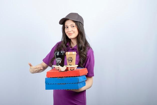 Доставщица в фиолетовой форме показывает коробки для пиццы и кофейные чашки. фото высокого качества