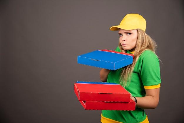 Доставщик в униформе, держа картоны пиццы.