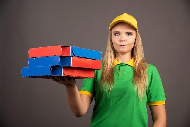 ピザの段ボールを保持している制服を着た配達員。