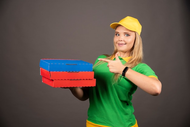 Доставщик в униформе, указывая на картоны пиццы.