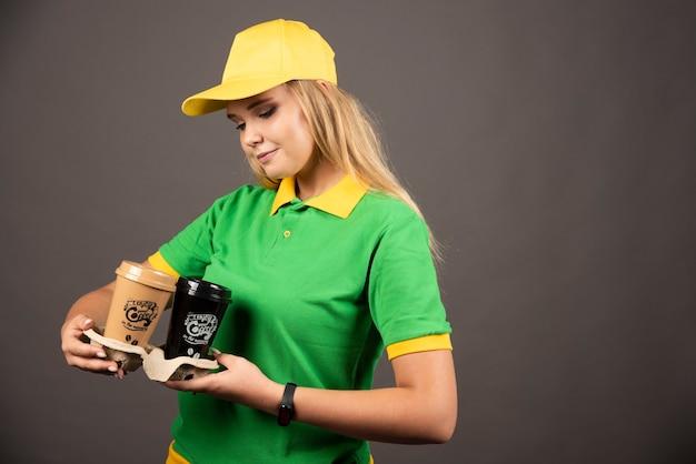 Fattorino che guarda le tazze di caffè sulla parete nera.