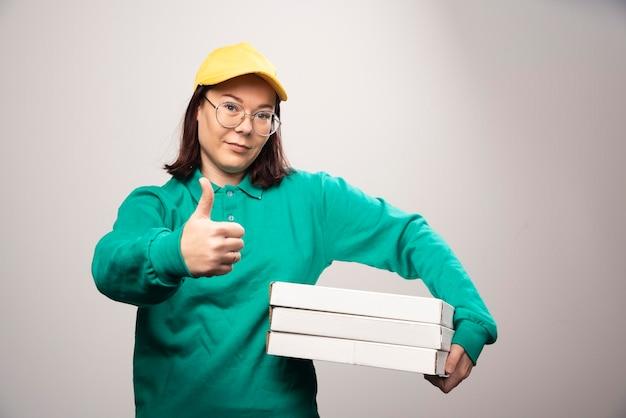 Fattorino che mostra un pollice in su e tiene in mano dei cartoni di pizza su un bianco. foto di alta qualità