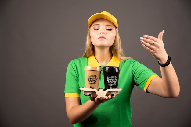 Deliverywoman sniffing cups of coffee on dark wall.