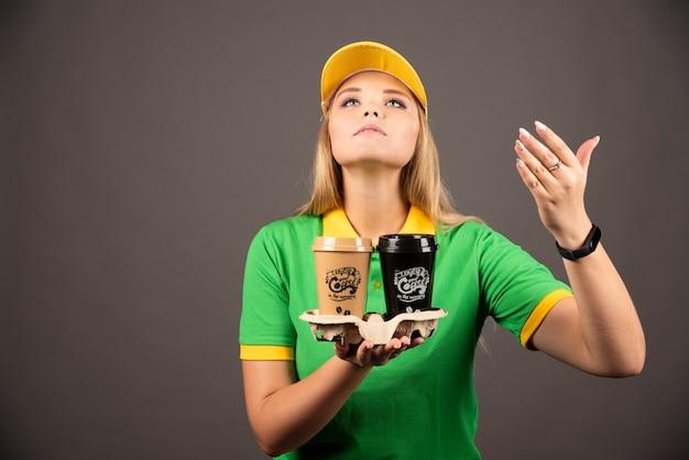 Доставщица нюхает чашки кофе на черной стене.
