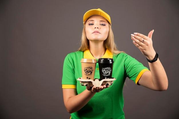 暗い背景にコーヒーのカップを嗅ぐ配達員。高品質の写真