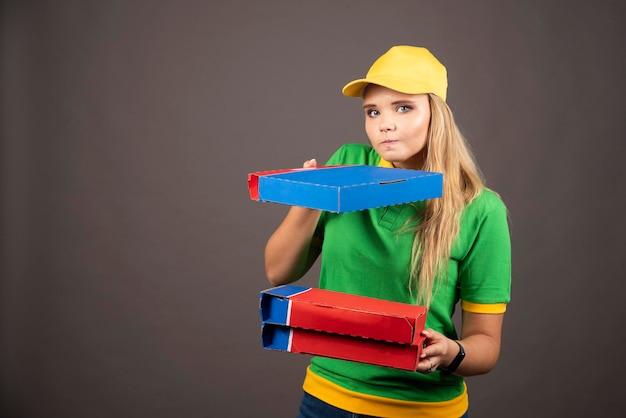 Deliverywoman in uniforme che tiene i cartoni di pizza. foto di alta qualità