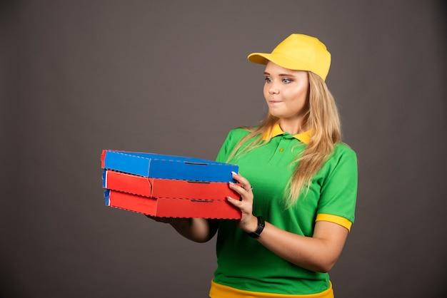Deliverywoman in uniforme che tiene i cartoni di pizza.