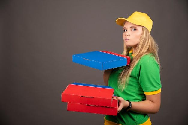Fattorino in uniforme che tiene cartoni di pizza.