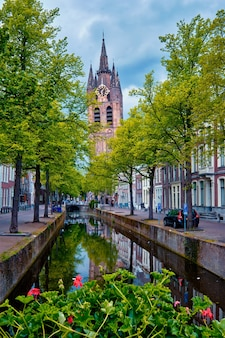 Delt canal with bicycles and cars parked along delft netherlands
