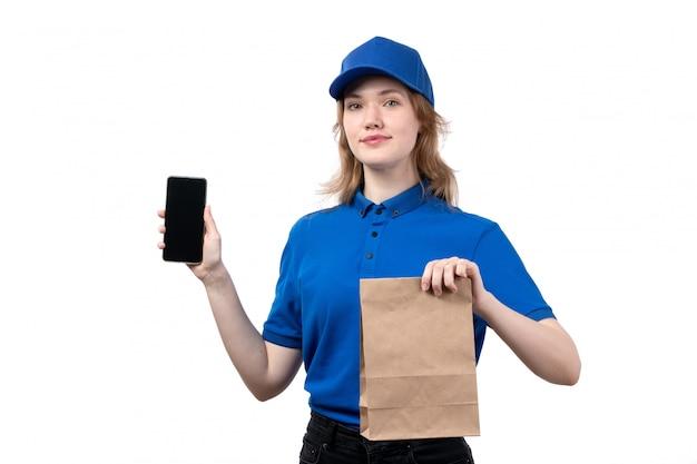 Вид спереди молодая женщина-курьер работница службы доставки еды держа смартфон и пакет delviery еды на белом фоне, предоставляя форму обслуживания