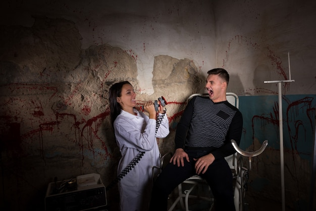 Demented female scientist holding electrical shocking devices in front of patient in dungeon with bloody walls in a halloween horror concept