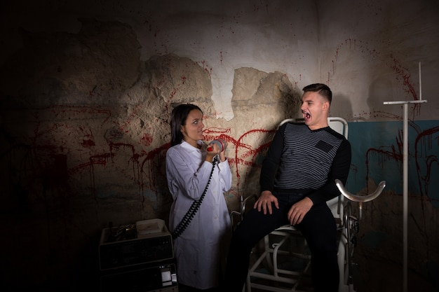 Demented scientist holding electrical shocking devices in front of patient in dungeon with bloody walls in a halloween horror concept