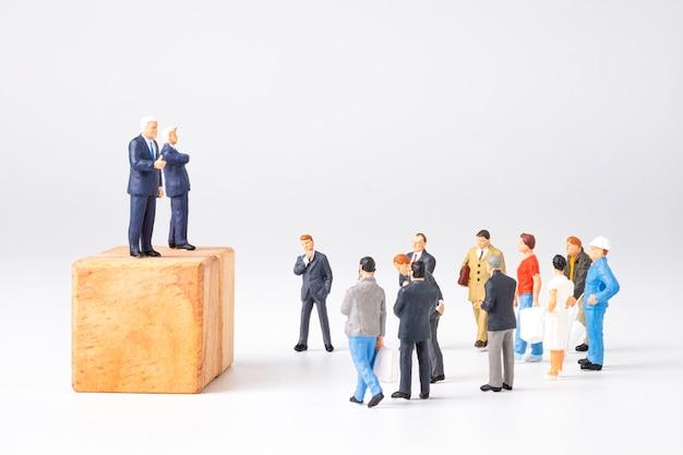 Концепция демократии и выборов президента и премьер-министра. две миниатюрные фигурки политиков объявляют, что общественность прислушивается к политике экономики и здравоохранения.