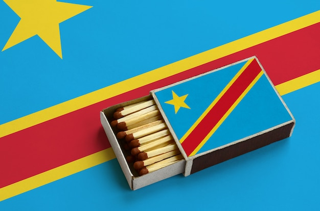 Democratic republic of the congo flag  is shown in an open matchbox, which is filled with matches and lies on a large flag