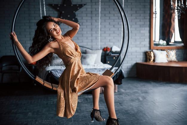 キュートな笑顔を披露。金色のドレスのきれいな女性は、チェーンのスタイリッシュな円形のベンチに座っています。ラグジュアリールーム