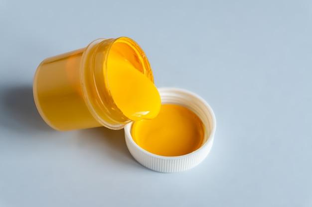 トレンディな色を示す2021-グレーとイエロー。黄色のガッシュペイントで缶を開けます。 Premium写真