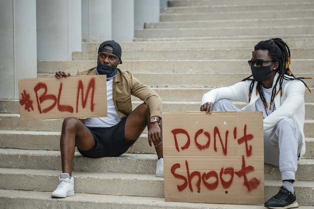 Демонстранты держат транспаранты с девизом движения за гражданские права чернокожих.