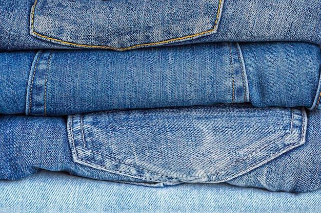 デニムの背景。ブルージーンズのさまざまな色合いの端正なスタック。洋服収納。