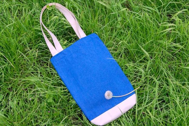 푸른 잔디의 배경에 데님 가방입니다. 텍스트, 모형을 위한 장소. 평면도.