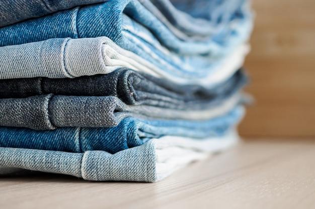 Denim blue jeans stack on wood table background