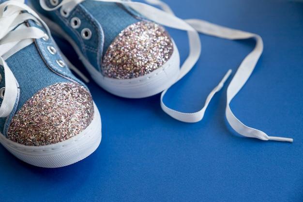 青色の背景にひもでデニムの子供の靴