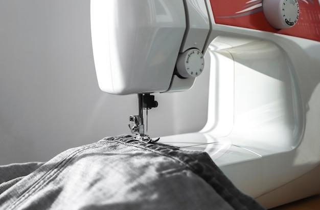 Джинсовая ткань на швейной машине крупным планом концепция малого бизнеса