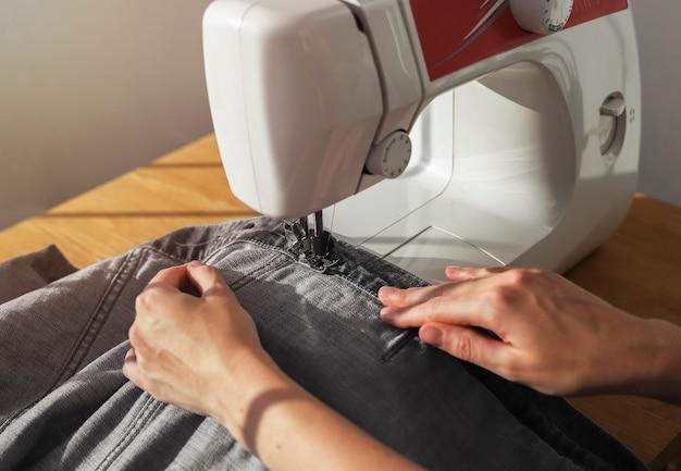 Джинсовая ткань на швейной машине крупным планом концепция рабочего процесса швеи