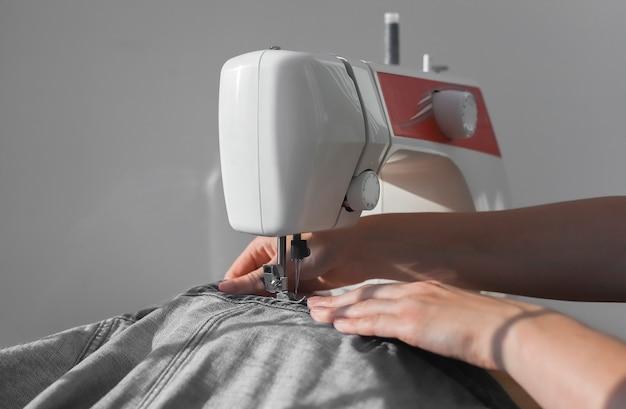 Джинсовая ткань на швейной машине крупным планом женские руки на ручной работе