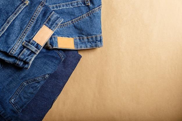 데님 옷. 다양한 데님 팬츠 모델 구색. 클래식한 청바지. 캐주얼 바지는 베이지색 공예 배경에 갈색 가죽 라벨이 붙은 청바지를 입고 복사 공간이 있습니다.