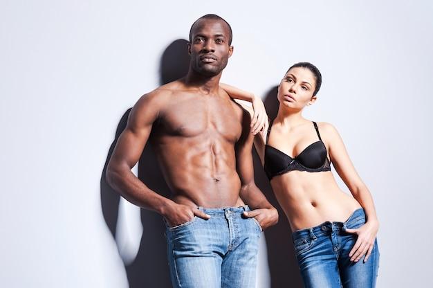 デニムカップル。灰色の背景に対して互いに近くに立っているジーンズの美しい若いカップル