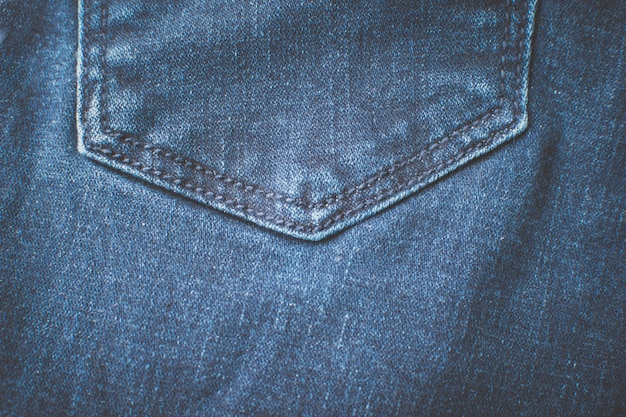 Denim fabric in blue. back pocket of jeans trousers