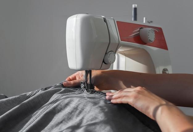 Джинсовая ткань на швейной машине крупным планом руки швеи на работе