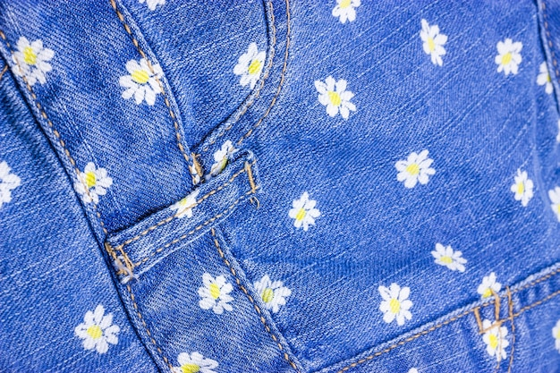Denim fabric with chamomile flowers background