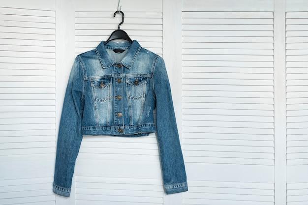 Джинсовая куртка на вешалке. модный гардероб