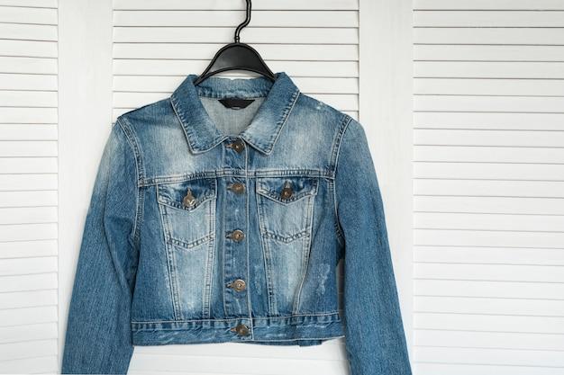Джинсовая куртка на вешалке на белой деревянной стене