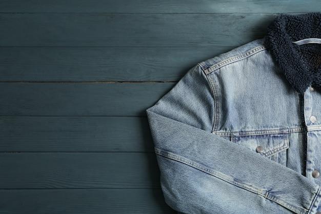 木製の背景にデニムジャケット、テキスト用のスペース木製の背景にデニムジャケット