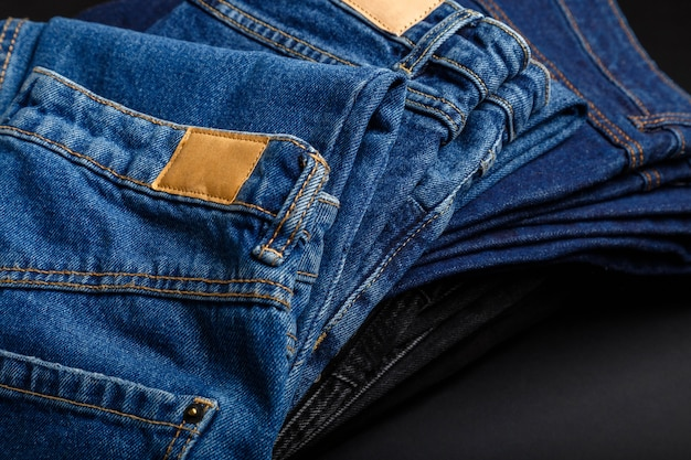 Denim jean pants folded in stack with empty brown tag mockup label. casual wear blue jeans stacked in pile on black background.