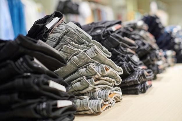 デニムジーンズは、現代のショッピングモールの衣料品店の上部にある木製のテーブルに積み重ねられます