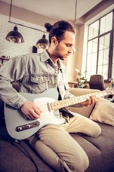デニムシャツ。新曲を構成するデニムシャツを着たひげを生やした黒髪の才能のあるミュージシャン