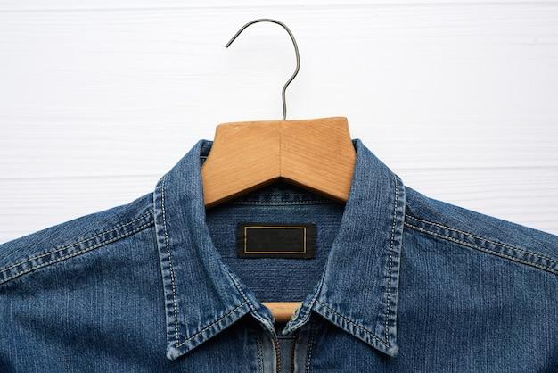 Джинсовая рубашка висит на деревянной вешалке