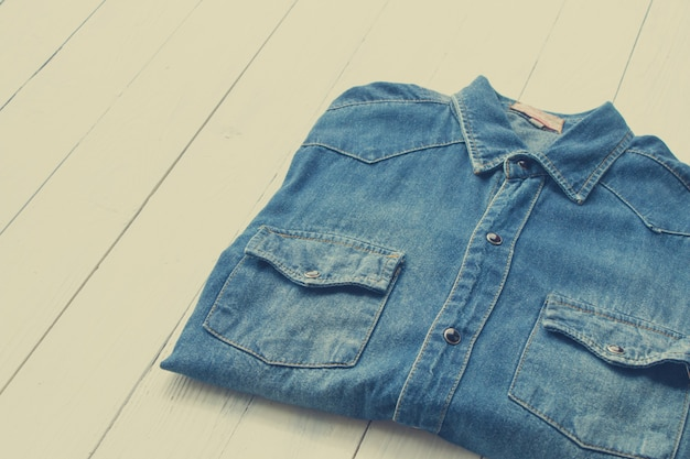 Denim shirt jeans put on wooden table background