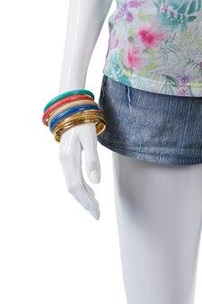 데님 반바지와 화려한 팔찌. 팔찌 세트를 착용하는 여성 마네킹. 손목 액세서리가 있는 여름 반바지. 십대 소녀들을 위한 유행 액세서리.