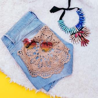 デニムショートパンツやファッションアクセサリー。サングラスとネックレス。