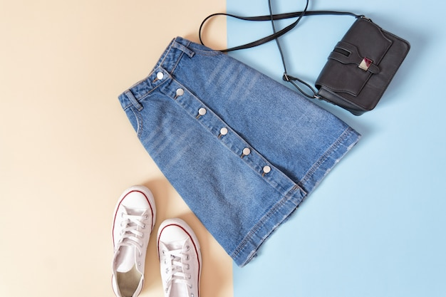 Denim skirt, handbag and white sneakers